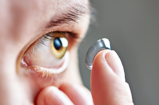 Young woman with astigmatism inserting a contact lens